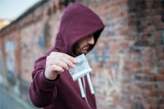 hooded man holds out bag of heroin