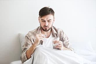 Man sits in bed about to take a buprenorphine or methadone pill
